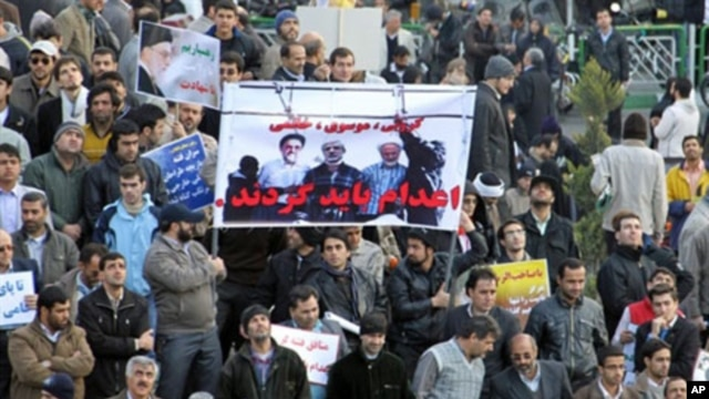 Iranian regime loyalists hold a poster with doctored pictures of former president Mohammad Khatami (L) and opposition leaders Mir Hossein Mousavi (C) and Mehdi Karroubi on the gallows during a pro-government demonstration in Tehran, February 18, 2011