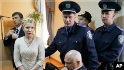 Police officers lead former Ukrainian Prime Minister Yulia Tymoshenko out of the courtroom after a verdict in her case has been rendered. (AP Photo/Efrem Lukatsky)