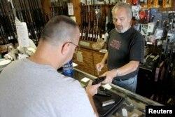 미국의 총기 판매점에서 판매자가 고객에게 총을 보여주고 있다. (자료사진)