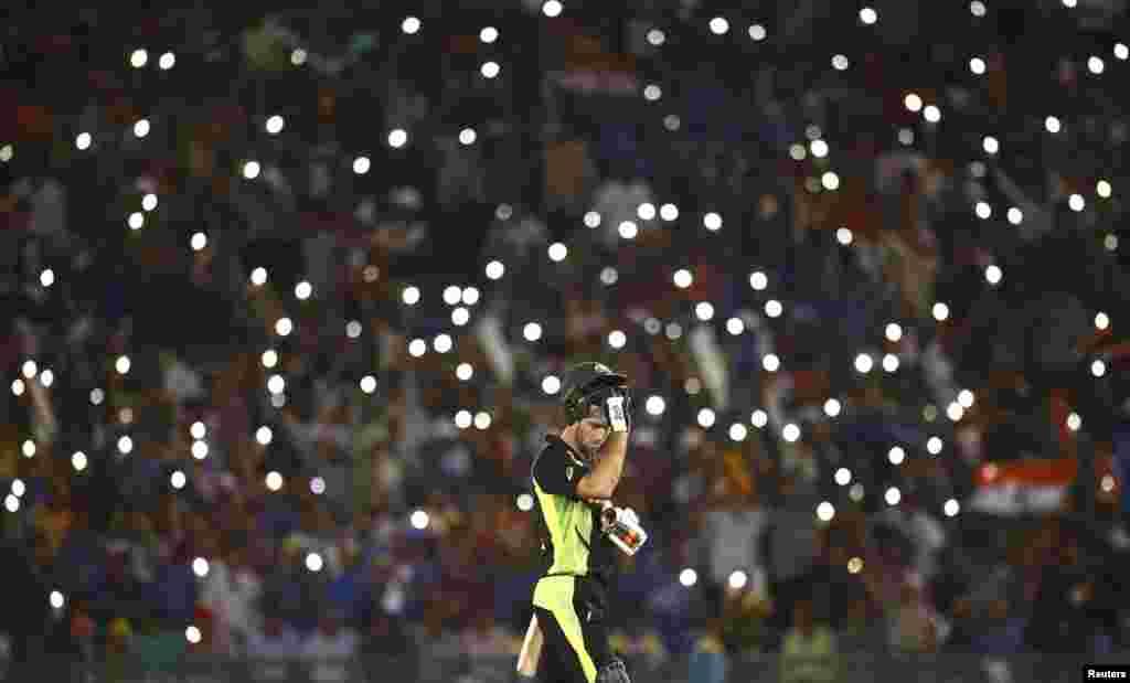 កីឡាករ Glenn Maxwell របស់អូស្រ្តាលីដោះមួកការពាររបស់គាត់ ដើម្បីញ៉ាំទឹក ក្នុងពេលប្រកួត World Twenty20 រវាងប្រទេសឥណ្ឌា និងអូស្រា្តលី នៅក្នុងក្រុង Mohali ប្រទេសឥណ្ឌា។