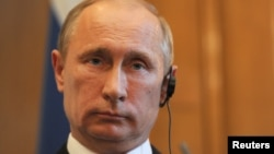 FILE - Russian President Vladimir Putin attends a news conference at 10 Downing Street, London, June 16, 2013.