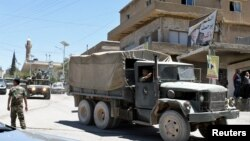 A convoy of Lebanese army soldiers drives at the entrance of the border town of Arsal, in eastern Bekaa Valley, Lebanon, June 30, 2017.