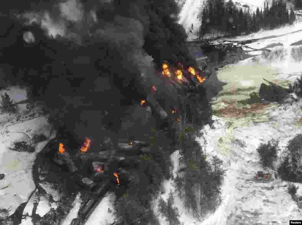 دود از آتش سوزی ترن راه آهنی برمیخيزد که از خط خارج شده است. اين ترن نفت خام حمل میکرد که در نزدیکی شهر شمالی گوگاما از خط خارج شد.