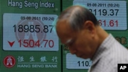 A man passes a screen displaying the Hong Kong Stock index, Aug. 2011 (file photo).