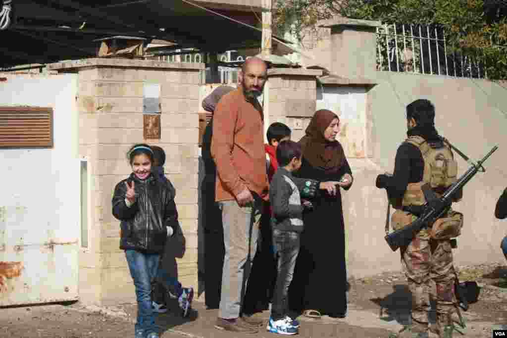 """2017年1月23日,六岁的阿娅打着胜利的手势,她的家人与伊拉克军人交谈,报告他们了解的有关""""伊斯兰国""""激进分子的信息。(美国之音希瑟·默多克拍摄)"""
