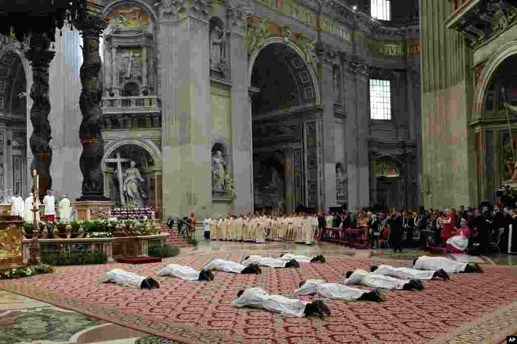 Ten new priests who were ordained by Pope Francis lay on the ground during a ceremony in St. Peter's Basilica at the Vatican.