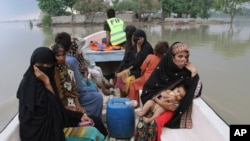 Pakistani volunteers rescue villagers from a flooded area in Layyah, Pakistan, July 25, 2015.