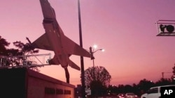 FILE - A mock F-16 fighter jet is silhouetted against the sky at sunrise at Moody Air Force Base at Valdosta, Ga., where two Afghan students who were receiving training went missing this week, Dec. 11, 2015.