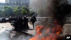 Des policiers anti-émeute devant une voiture renversée lors d'une manifestation des chauffeurs de taxi, le jeudi 25 Juin, 2015 Paris, France.