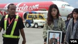 Kerabat Oscar Desano membawa fotonya di depan pesawat AirAsia yang membawa jenazah pramugara maskapai tersebut di Bandara Adi Sumarmo, Solo (14/1). (VOA/Yudha Satriawan)