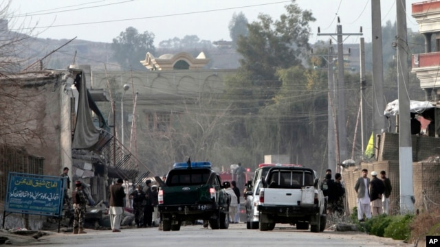 Security officials investigate the scene of a suicide car bomb attack, which killed and injured several people at the National Directorate of Security in Jalalabad, Afghanistan, February 24, 2013.