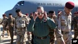Iraqi Defense Minister Khaled al-Obeidi, center, arrives at a military a base outside Tikrit, 130 kilometers (80 miles) north of Baghdad, Iraq, March 9, 2016.