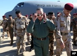 Iraqi Defense Minister Khaled al-Obeidi (c) arrives at a military a base outside Tikrit, 130 kilometers (80 miles) north of Baghdad, Iraq, March 9, 2016.
