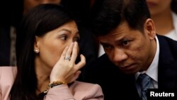 FILE - Maia Santos Deguito, a branch manager of the Rizal Commercial Banking Corp (RCBC), whispers to her lawyer as she testifies during a Senate hearing on money laundering involving $81 million stolen from Bangladesh central bank, at the Philippine Senate in Manila, April 12, 2016.