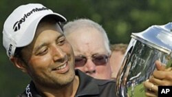 Arjun Atwal, of India, holds the Sam Snead Cup on the 18th green after winning the Wyndham Championship golf tournament in Greensboro, N.C, 22 Aug 2010