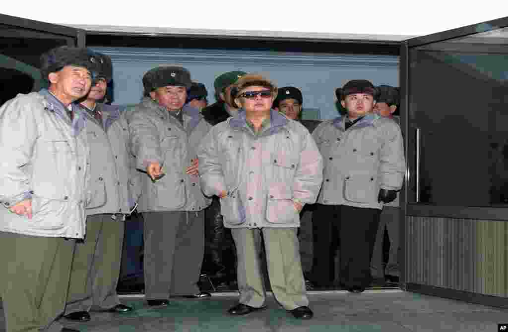 North Korean leader Kim Jong Il (C), accompanied by his son Kim Jong Un (R), inspecting Korean People's Army Air Force Unit 1016 honored with the title of O Jung Hup-led Seventh Regiment at undisclosed place in North Korea, undated handout picture. (AFP)