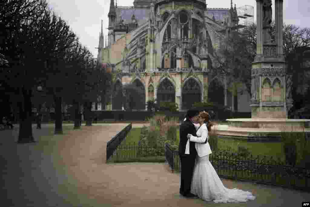 Two people kiss after renewing their wedding vows on Valentine's Day, behind Notre Dame Cathedral in Paris, France.
