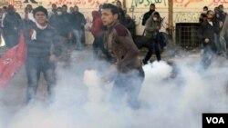 Para demonstran menghindari gas air mata yang ditembakkan pasukan keamanan Mesir di Kairo, Minggu (5/2).