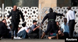 FILE - People run for cover as gunshots are fired from inside the Taj Mahal hotel in Mumbai, Nov. 27, 2008. In 2008, 10 heavily armed gunmen mounted coordinated raids that lasted three days.
