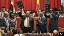 Sudan's President Omar al-Bashir, center-left, and South Sudan President Salva Kiir, right, celebrate the completion of a signing ceremony in Addis Ababa, Ethiopia, September 27, 2012.