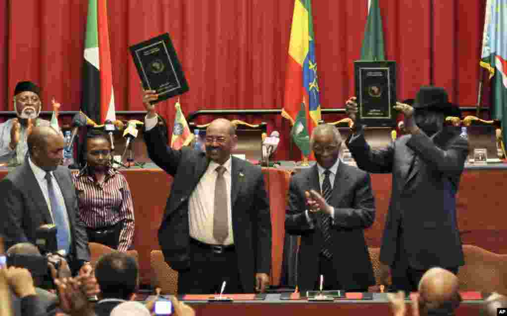 Sudan's President Omar al-Bashir, center-left, and South Sudan President Salva Kiir (r) celebrate the signing of 9 agreements, in Addis Ababa, Ethiopia, September 27, 2012.