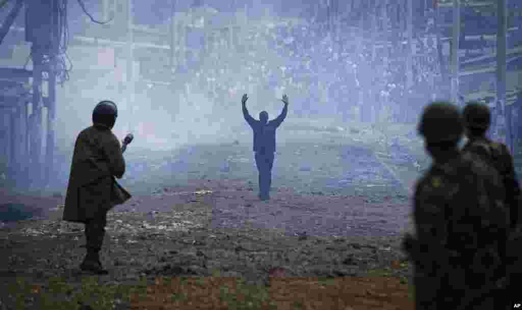 تظاهرکننده اهل کنیا با دستهای بالا و از میان غباری از گاز اشک آور خود را به پلیس ضدشورش تسلیم می کند. آنها می گویند در انتخابات تقلب شد.