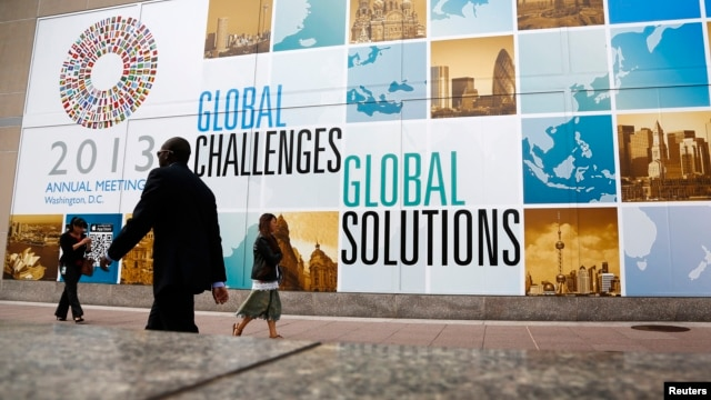 People walk outside the International Monetary Fund headquarters at the start of the annual IMF-World Bank fall meetings in Washington, Oct. 8, 2013.