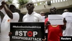 People protesting against xenophobia in South Africa hold placards in front of the South African consulate in Lagos, April 16, 2015.