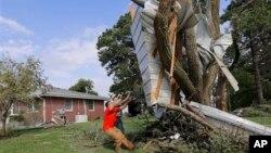 Residentes en Bennet, Nebraska, tratan de desprender la sección lateral de una casa incrustada en un árbol.
