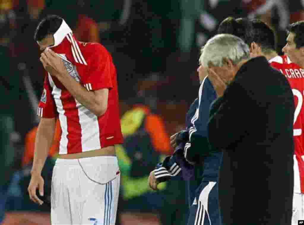 Paraguay's Oscar Cardozo, left, covers his face with his jersey at the end of the World Cup quarterfinal soccer match between Paraguay and Spain at Ellis Park Stadium in Johannesburg, South Africa, Saturday, July 3, 2010. Spain won 1-0 and Cardozo missed