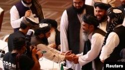 Delegasi Taliban berjabat tangan selama pembicaraan antara pemerintah Afghanistan dan gerilyawan Taliban di Doha, Qatar 12 September 2020. (Foto: REUTERS/Ibraheem al Omar)