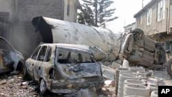 Xe bồn chở xăng bị nằm cạnh một chiếc xe bị phá hủy sau vụ nổ ở ngoại ô Ecatepec, ngày 7/5/2013.