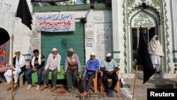مسلمانوں کا ایک گروپ ایودھیا میں متنازع بابری مسجد کے باہر بیٹھا ہے۔ بھارت میں مسلمانوں کی تعداد کل آبادی کے 14 فی صد سے زیادہ ہے۔