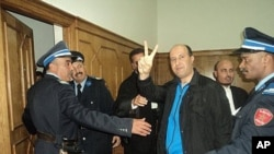 Rachid Nini being escorted into the courtroom in Morocco