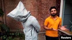 "Saud Baloch, 28, a fine art artist, stands near his sculpture called ""No Fear"" during an interview at the National College of Arts in Lahore, March 22, 2013"