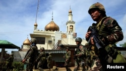Government troops walk past a mosque before their assault on insurgents from the so-called Maute group, who have taken over large parts of Marawi City, southern Philippines, May 25, 2017.