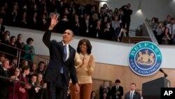 Presiden Amerika, Barack Obama dan ibu negara Michelle Obama melambaikan tangan kepada para hadirin seusai menyampaikan sambutan di Belfast Waterfront Hal, Belfast, Irlandia Utara, (17/6). Presiden Obama mengunjungi Irlandia Utara untuk menghadiri KTT G-8 yang diselenggarakan selama dua hari di Enniskillen.