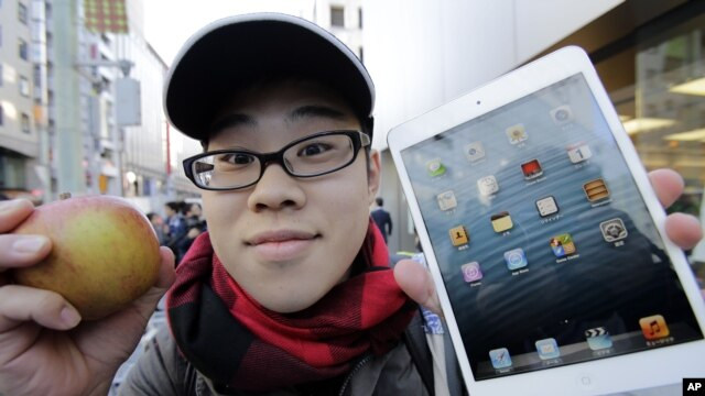 A customer, Koudai Taguchi,19, poses for photographers with Apple's iPad Mini after he bought at a store in Tokyo Friday morning, Nov. 2, 2012.