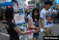 學民思潮成員(左一)在旺角街頭向途人派發反國民教育宣傳單