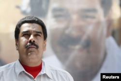 FILE - Venezuela's President Nicolas Maduro stands in front of a picture of himself during a meeting with government workers in Caracas, Nov. 20, 2015.