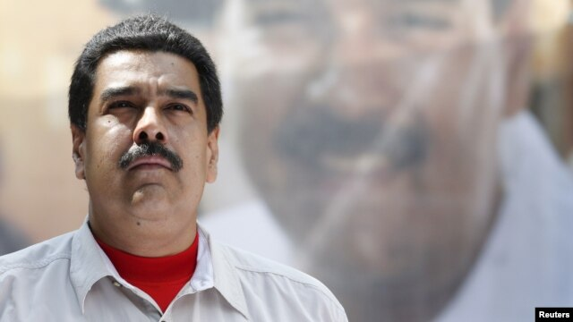 FILE - Venezuela's President Nicolas Maduro stands in front of a picture of himself during a meeting with government workers in Caracas.