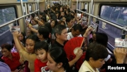 FILE - Commuters ride a train during rush hour on Southeast Asia's first light rail transit network, which is 29-years-old, in Manila, Oct. 10, 2013. The Philippines is about to spend $169 billion on infrastructure, including railways and an airport terminal.
