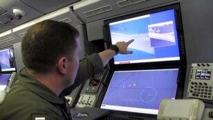 A U.S. Navy crewman aboard a P-8A Poseidon surveillance aircraft views a computer