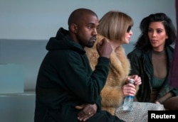 FILE - Singer Kanye West watches models rehearse while sitting with his wife Kim Kardashian (R) and Anna Wintour before presenting his Fall/Winter 2015 partnership with Adidas at New York Fashion Week .