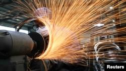 浙江杭州市一名戴著口罩的工人在生產自行車輪子鋼圈的生產線上工作。(2020年3月2日)