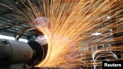 浙江杭州市一名戴著口罩的工人在生產自行車輪子鋼圈的生產線上工作。 (2020年3月2日)