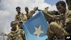 Soldiers of the Somali National Army (SNA) are seen displaying the Somali national flag in Saa'moja, around 7km north-west of the port city of Kismayo, in southern Somalia, Monday, Oct. 1, 2012. (AP Photo/AU-UN IST, Stuart Price)