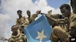 Beberapa tentara Somalia mengibarkan bendera nasional (foto: dok). PBB memperlonggar embargo senjata atas militer Somalia.