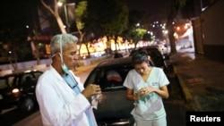 Deux médecins prenant une collation pendant dans une station-service lors de la quarantaine nationale en raison de l'épidémie de coronavirus, Caracas, Venezuela, 7 avril 2020. (Reuters/Manaure Quintero)