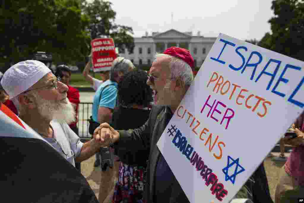 Samir Hineidi, of Fairfax, Virginia, left, and a demonstrator who chose not to be identified, participate in a Middle East demonstration outside the White House in Washington.